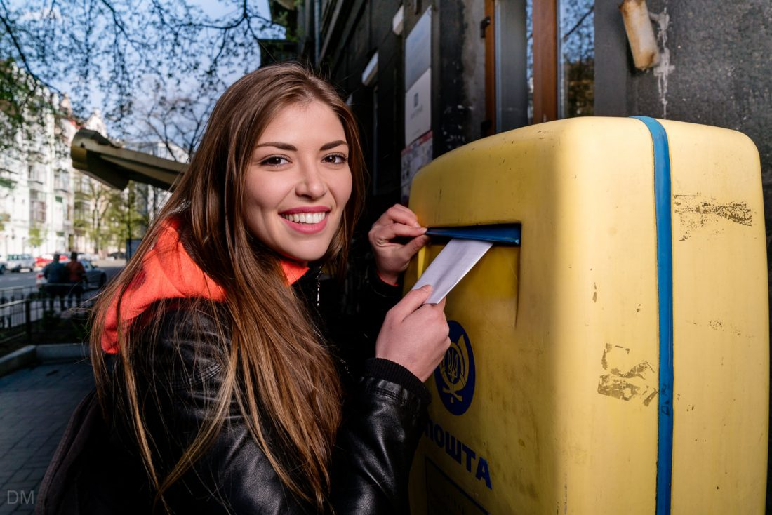 Beautiful Ukrainian girl posting a letter in a post box in Kiev, Ukraine