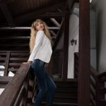 Tall blonde female model standing on wooden stairway at Perchersk Lavra in Kiev, Ukraine