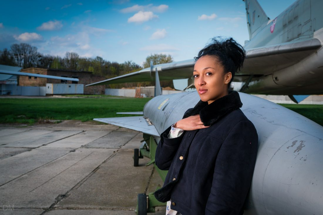 Girl standing next to a missile and jet fighter at the State Aviation Museum in Kiev, Ukraine