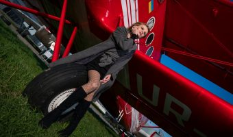 Girl standing next to a red biplane at the State Aviation Museum in Kiev, Ukraine