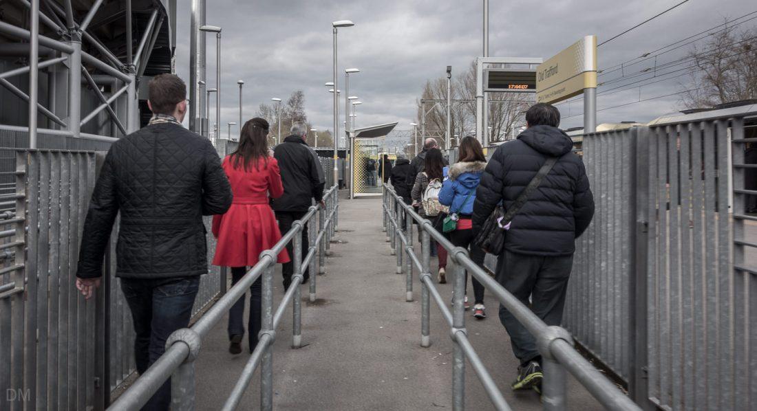 Manchester United fans walking to the platform at Old Trafford Metrolink Station
