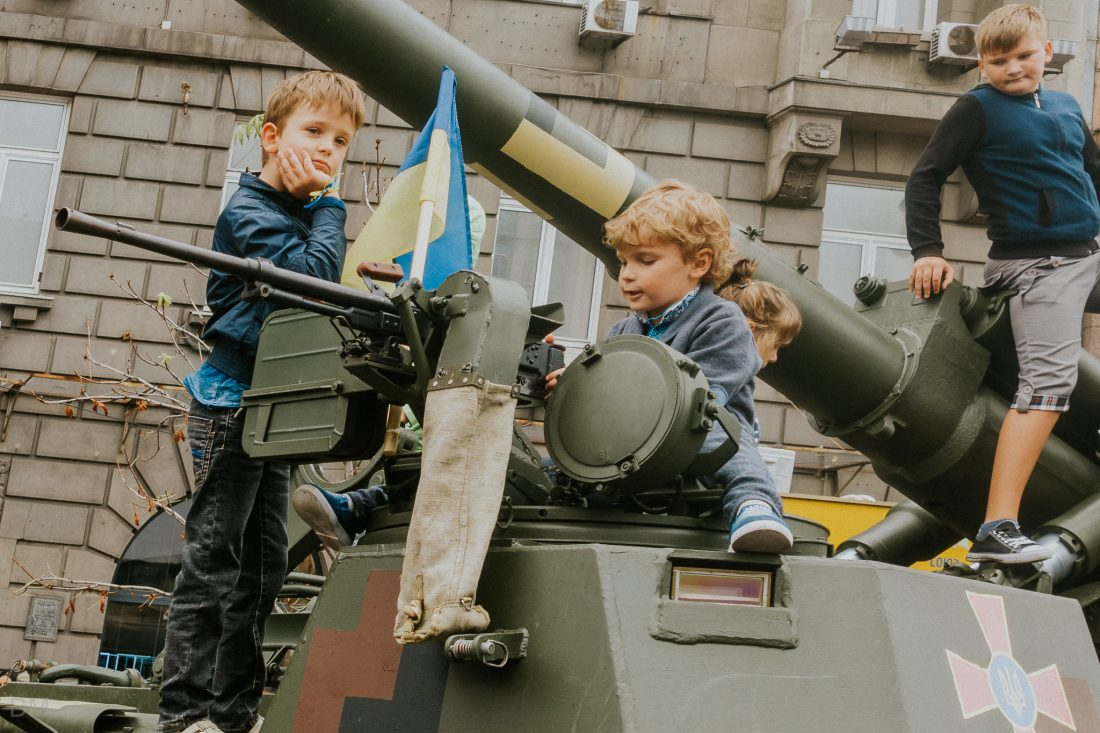 Children sitting on top of a tank in Kiev, Ukraine