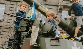 Children sitting on top of a tank in Kiev, Ukraine