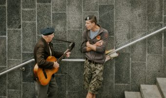 Soldier of a Ukrainian paramilitary force being serenaded by an army veteran in Kiev, Ukraine