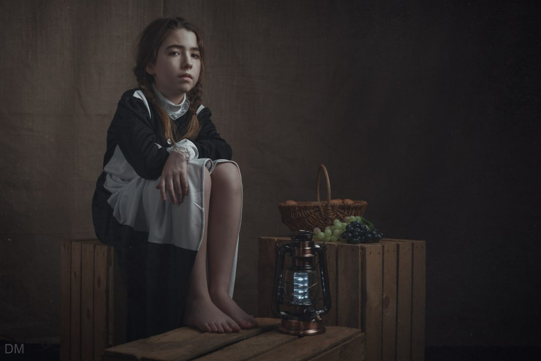 Girl dressed as a maid, sitting on apple crates. Fine art photography.