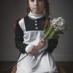 Photograph of a girl wearing a maid's costume and holding a flower