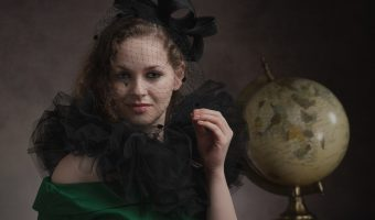 Model wearing a 1920s dress sat with a globe