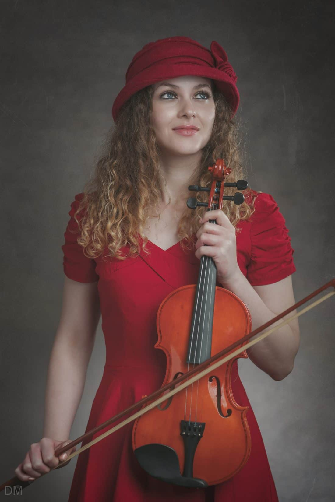 Model in a red dress and red hat holding a violin