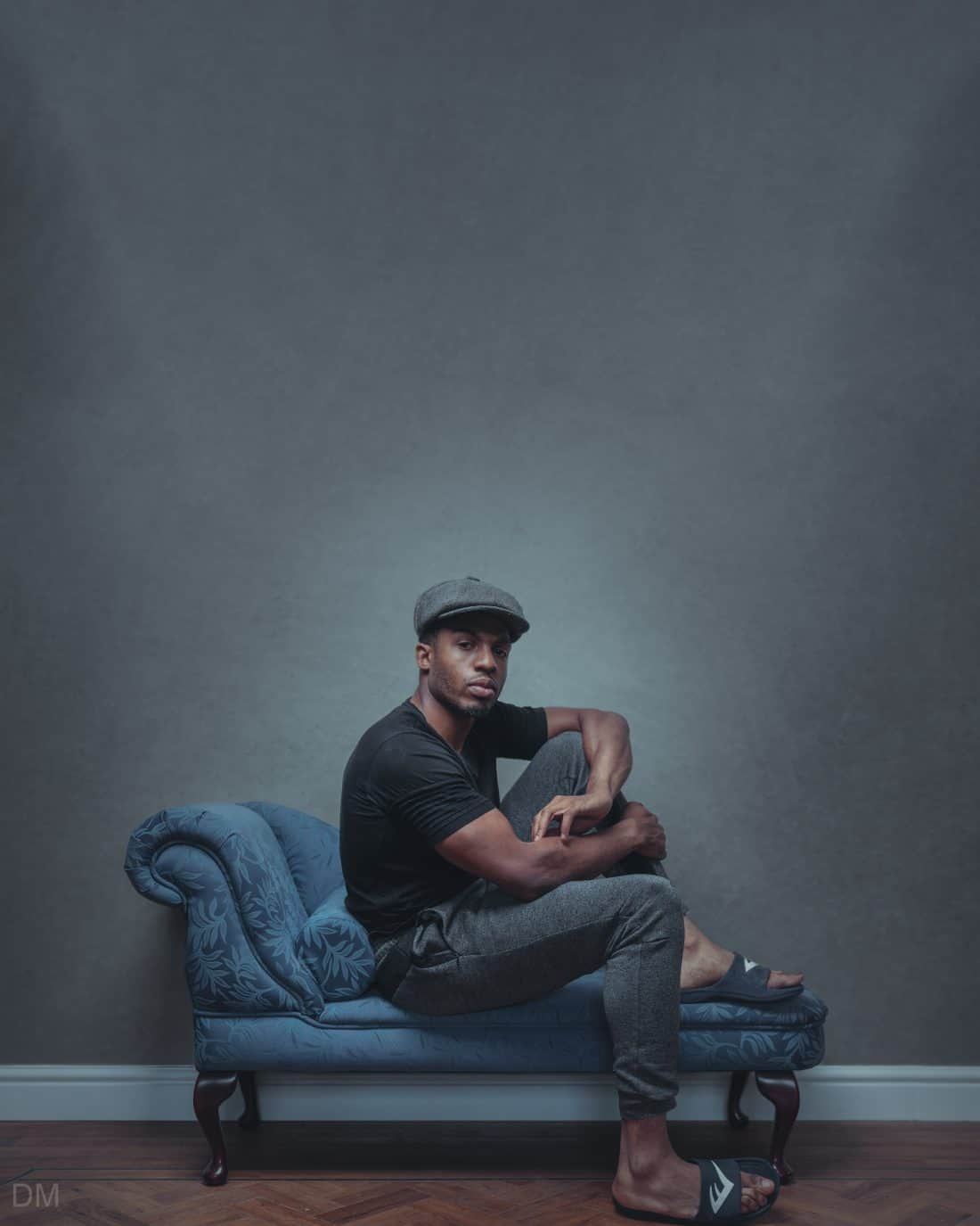 Photograph of a black man sitting on a chaise longue