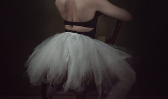 Ballerina in a white tutu sat on a chair.