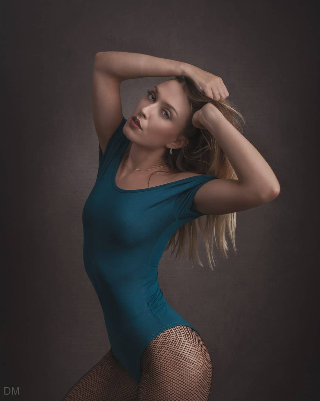 Photograph of a French model wearing a blue bodysuit