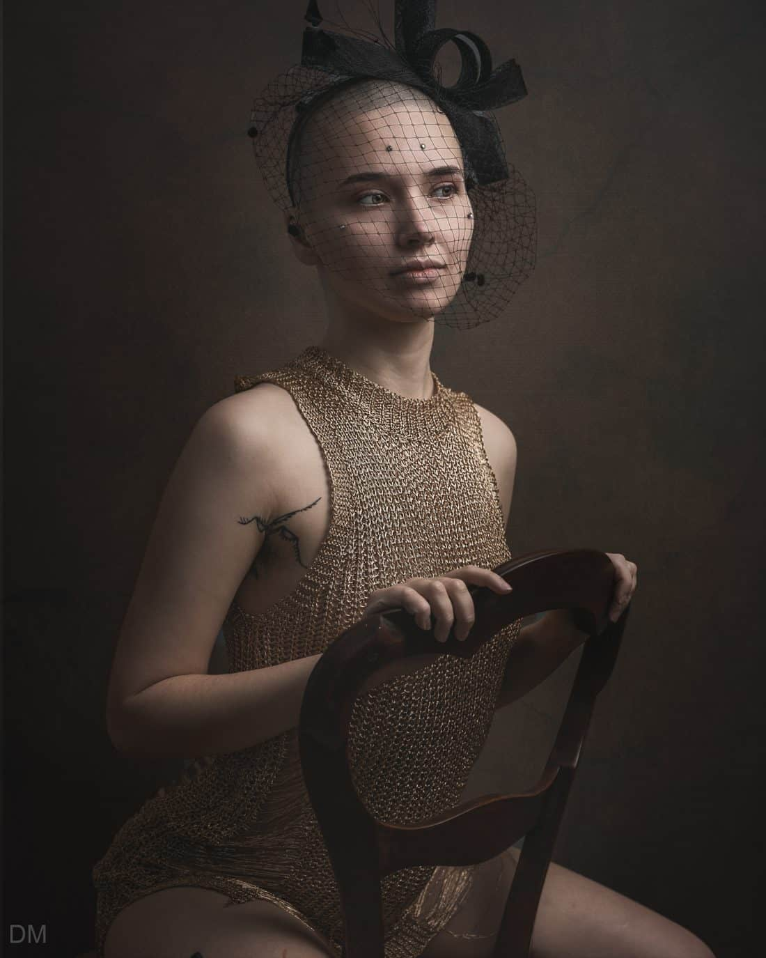 Androgunous female model sitting on a chair in a gold dress