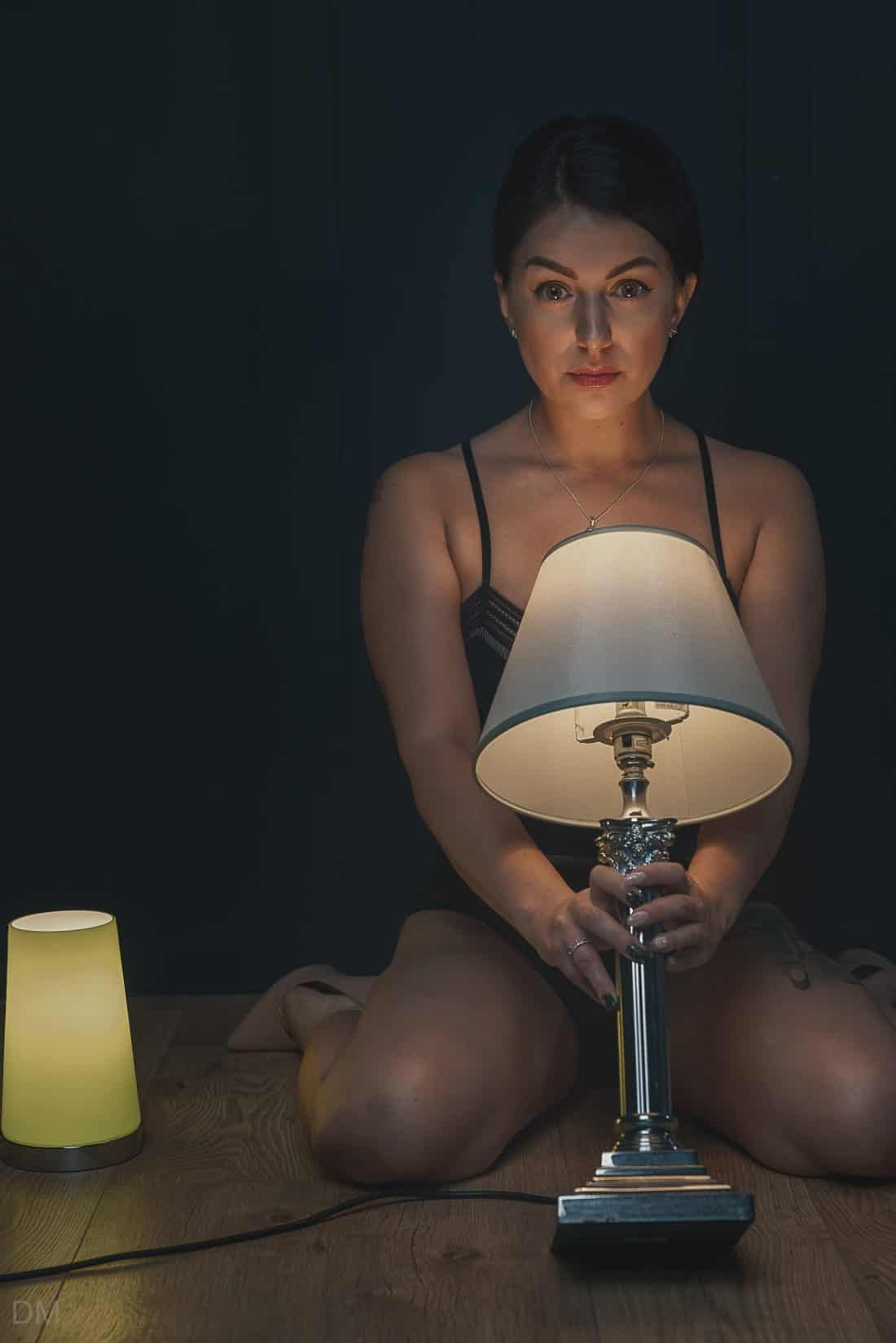 Photograph of female model holding a table lamp
